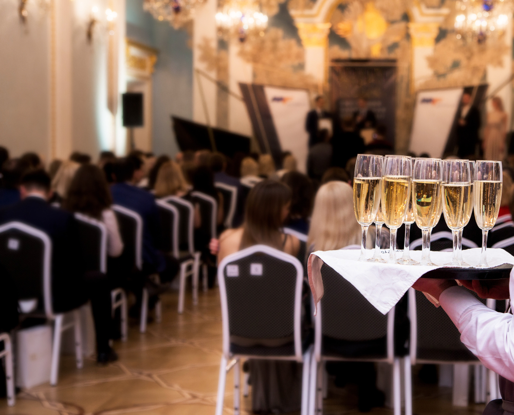 photo of waiter offers champagne to guests at the event